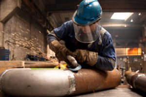 welder grinding away on pipe in workshop